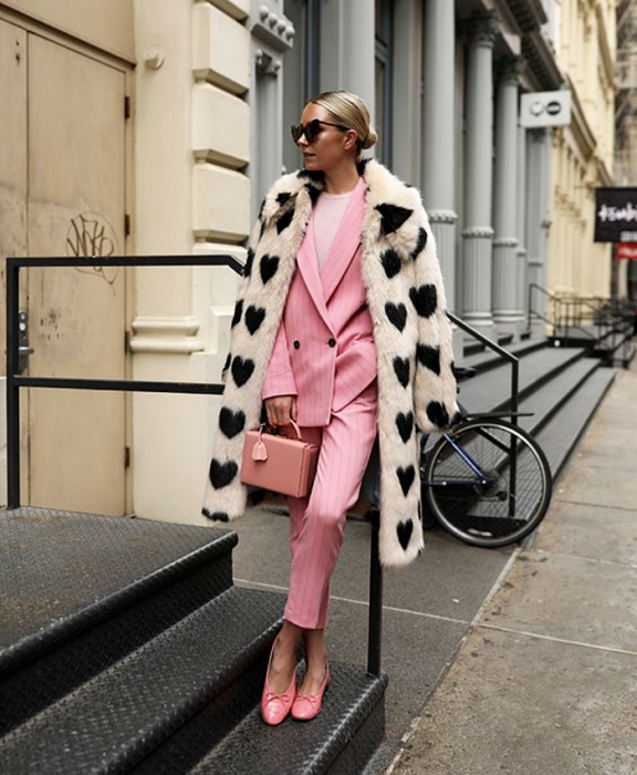 blonde girl wearing sunglasses, white coat with black hearts, pink jacket, pink dress pants, pink flats and pink bag, white top underneath