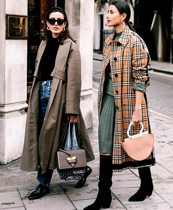 brown haired girl wearing sunglasses, black top, long brown coat, jeans, black loafers and gray handbag, brown haired girl wearing blue sweater, blue knitted skirt, long black high heeled boots and long burberry coat with orange handbag
