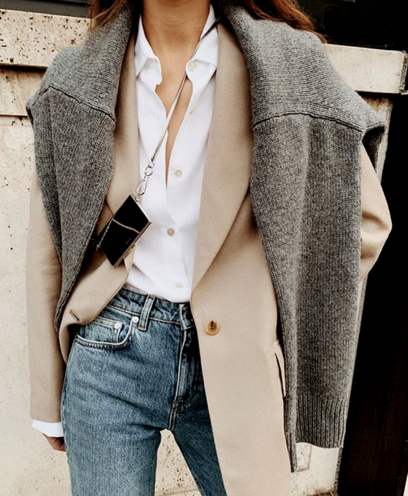 brown-haired girl wearing gray sweater, beige jacket, white shirt and jeans at the waist with mini metal bag