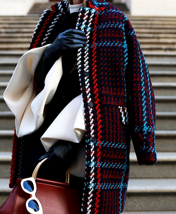 girl wearing a white blouse, black sweater, leather gloves, long blue, red, white and light blue plaid coat, red handbag and white sunglasses