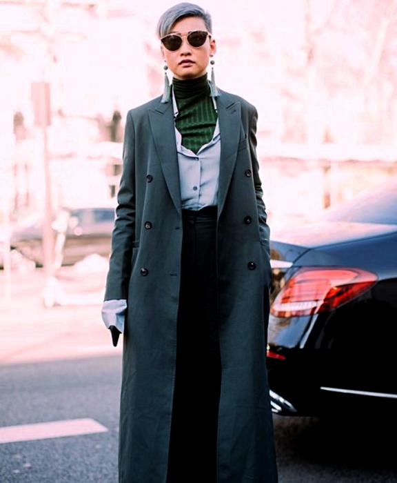 gray haired girl wearing sunglasses, green turtleneck top, light blue dress shirt, long dark gray coat and black dress pants