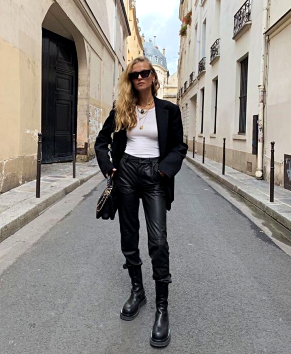 blonde girl wearing sunglasses, white top, big black blazer, leather pants, black leather ankle boots and black handbag