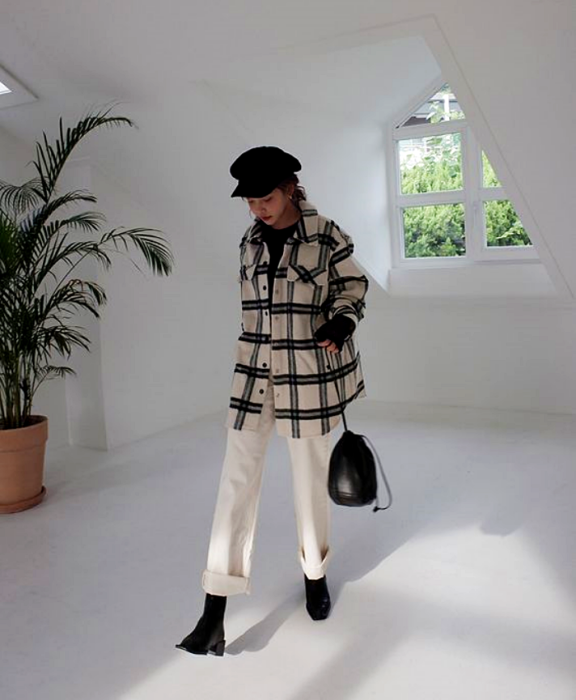 girl wearing black hat, white coat with black lines, white pants, black ankle boots and black bag