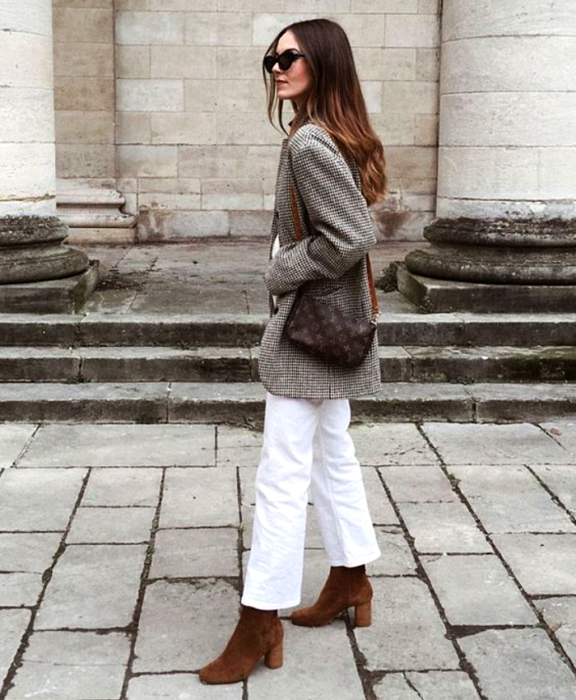 girl with long brown hair with sunglasses, gray coat jacket, white pants, brown bag and brown velvet ankle boots