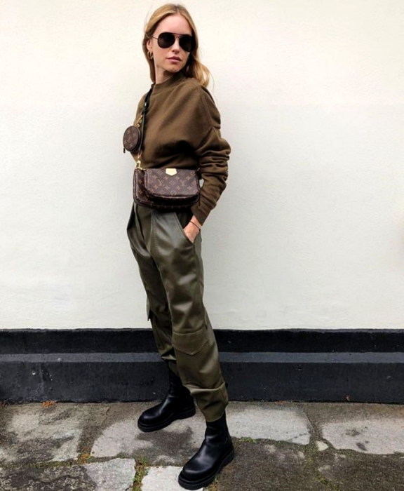 blonde girl wearing sunglasses, dark brown sweatshirt, handbag, army green pants and black leather boots with thick soles