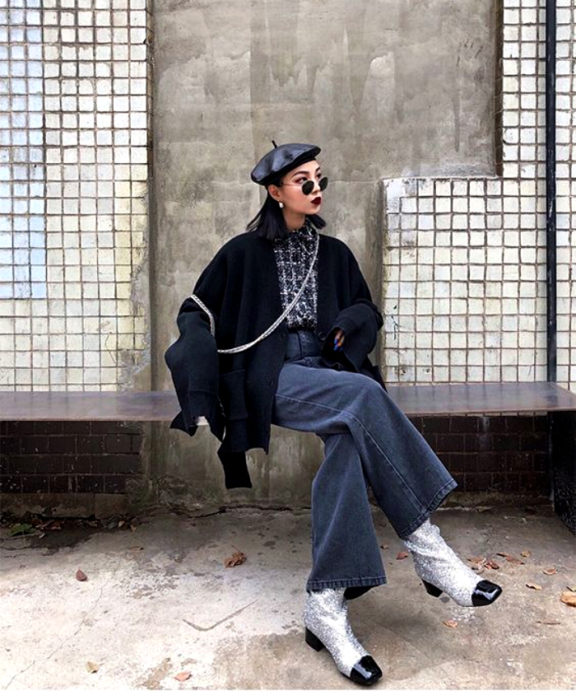 short haired girl wearing beret, sunglasses, collared shirt with print, oversized black cardigan, flared jean pants and silver ankle boots with diamond and black tip