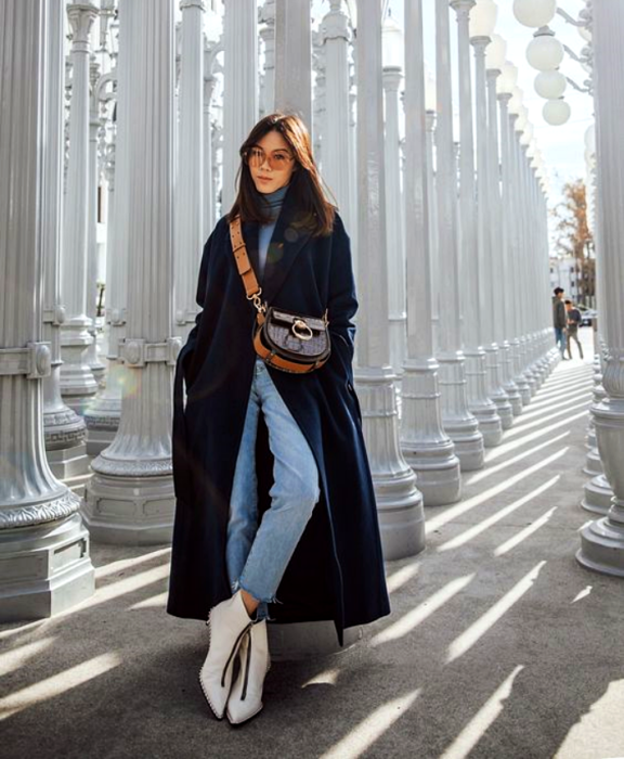 girl with long brown hair wearing sunglasses, light blue high neck top, long navy blue coat, jeans, white leather ankle boots and brown bag