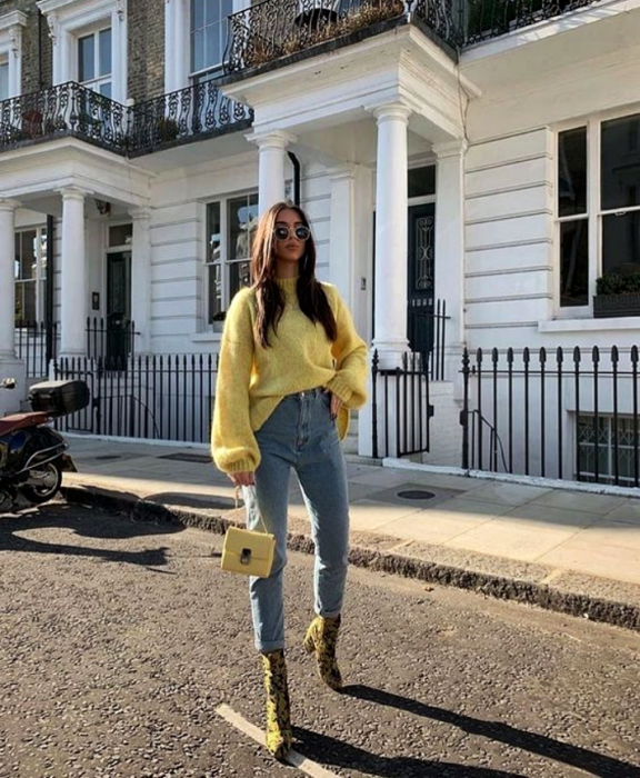 girl with long brown hair wearing sunglasses, yellow sweater, yellow mini bag, skinny jeans and yellow ankle boots with black