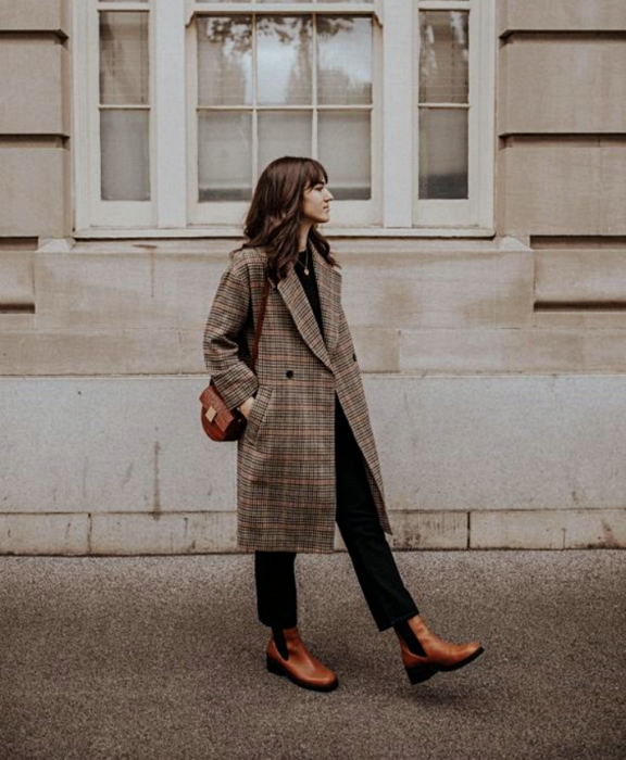 brown-haired girl in long brown coat, brown handbag, black jeans and brown leather ankle boots
