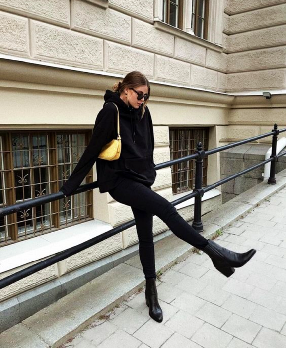 girl wearing sunglasses, black sweatshirt, black skinny jeans and black leather heeled ankle boots