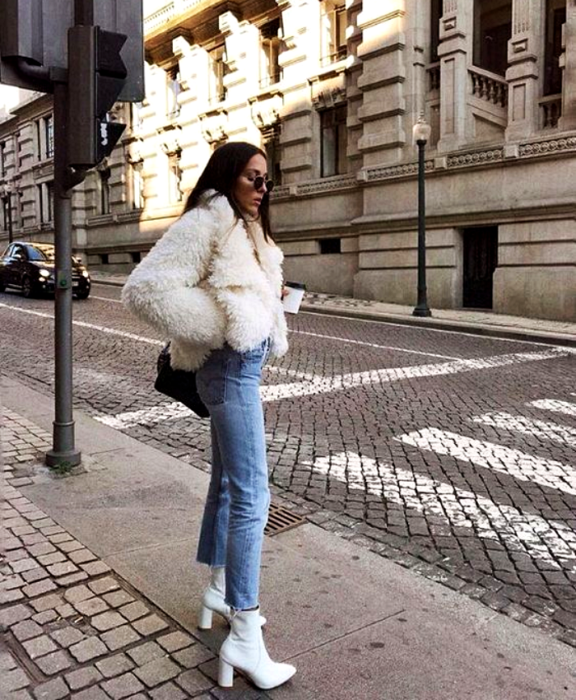 girl with long brown hair wearing sunglasses, white teddy type coat, skinny jeans, white leather ankle boots with heel and black handbag