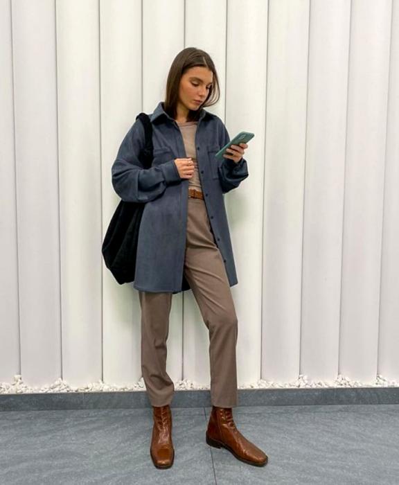 chica con cabello castaño usando un abrigo azul, top beige, pantalones beige, bolso negro, botines cafés de cuero