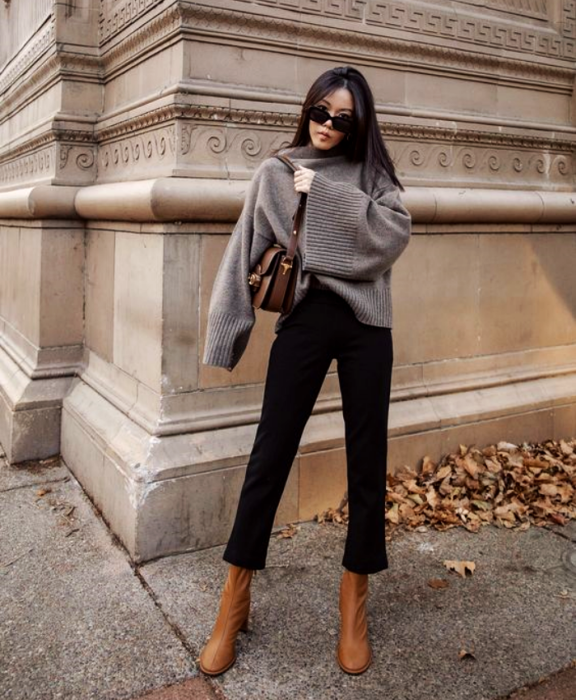 Brown haired girl wearing sunglasses, gray sweatshirt, black pants, patterned bag, light brown leather ankle boots