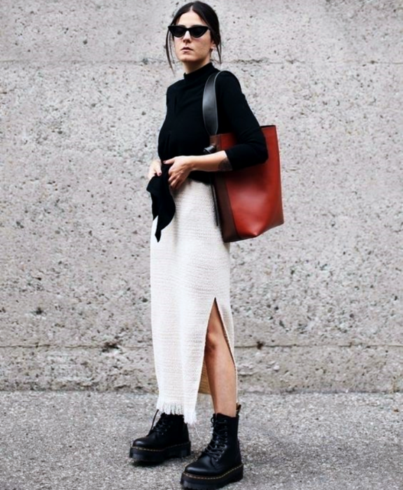 dark-haired girl wearing sunglasses, black sweater, red handbag, long white skirt, black thick-soled ankle boots