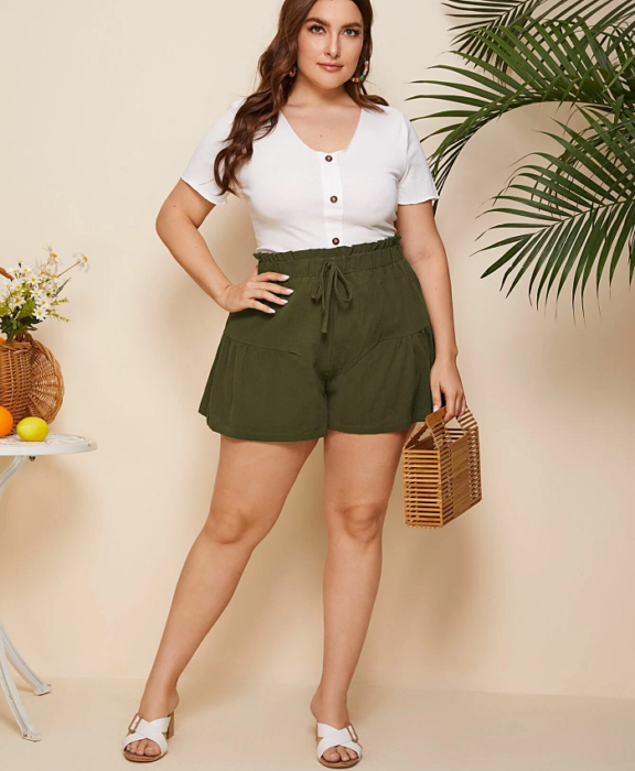 curvy girl wearing white V-neck button-down top, green paperbag shorts and small brown tote bag