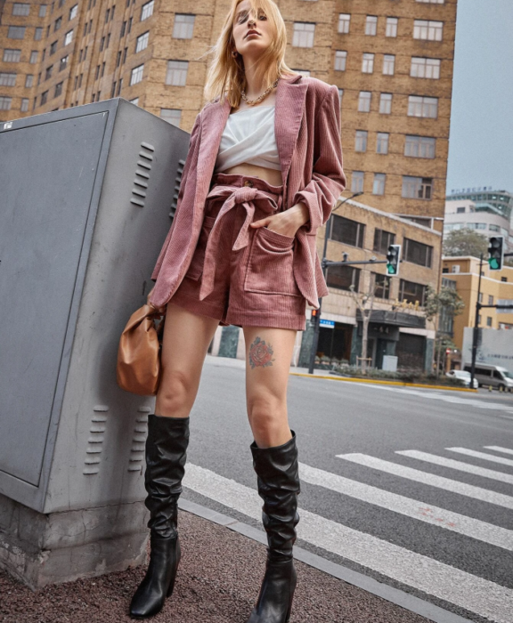 blonde girl wearing white top, pink corduroy blazer jacket, pink corduroy paperbag shorts and long leather heeled boots and brown clutch bag