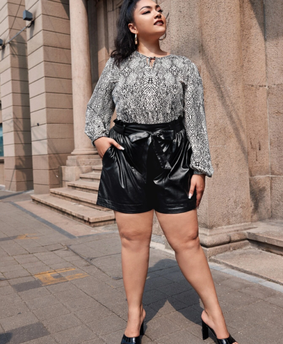 Curvy brunette girl wearing white blouse with black long sleeves, paperbag black leather shorts and black heeled sandals