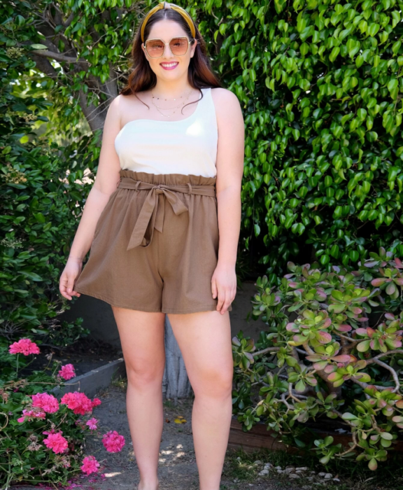 Curvy girl with long brown hair wearing sunglasses, white tank top, beige paperbag shorts
