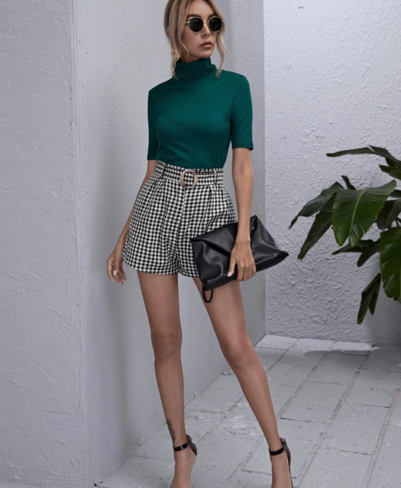 blonde girl wearing sunglasses, green top with high neck, white plaid paperbag shorts with black and high heels