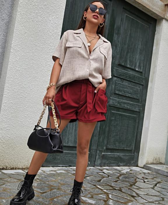 chica de cabello castaño con lentes de sol, camisa blanca de manga corta, paperbag shorts rojos, botines negros de piel y bolso de mano