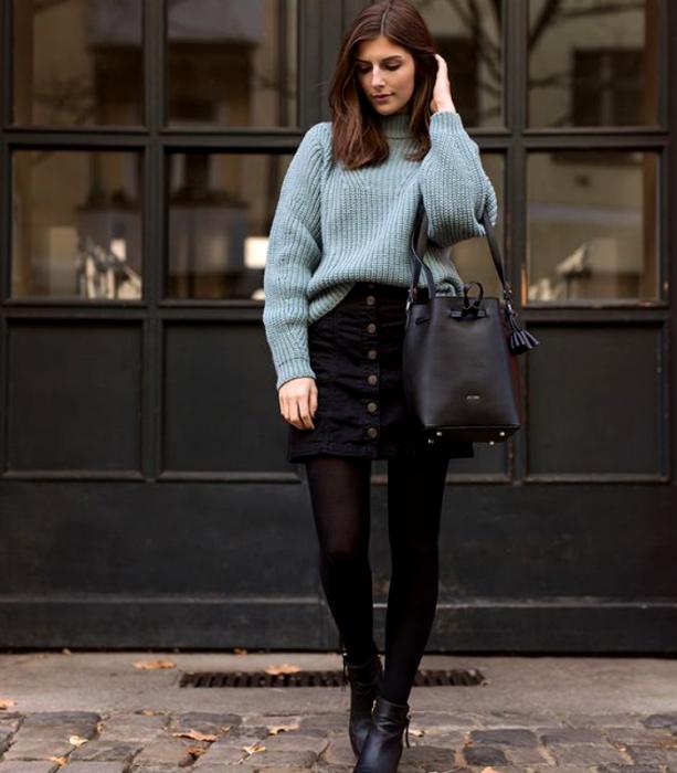 chica de cabello castaño usando un suéter azul celeste, minifalda de mezclilla negra, medias negras