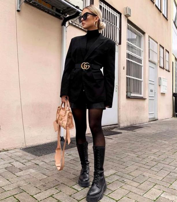 chica rubia usando lentes de sol, abrigo negro con cinturón con hebilla, minifalda negra, medias negras y botas gruesas de cuero