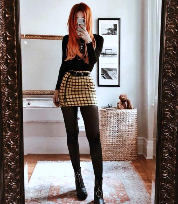 redhead girl wearing long sleeve shirt, yellow miniskirt with black, black tights and black leather ankle boots