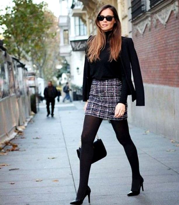 chica de cabello largo castaño usando lentes de sol, camiseta de manga larga, minifalda de cuadros, medias negras y zapatos de tacones