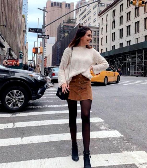 chica de cabello castaño largo con suéter blanco, falda café de pana, medias negras y botines negros y bolso pequeño