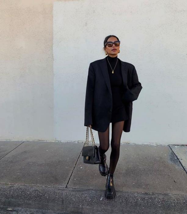 chica de cabello oscuro, lentes de sol, camiseta de manga larga, blazer oversized, medias negras, minifalda negra y botines negros
