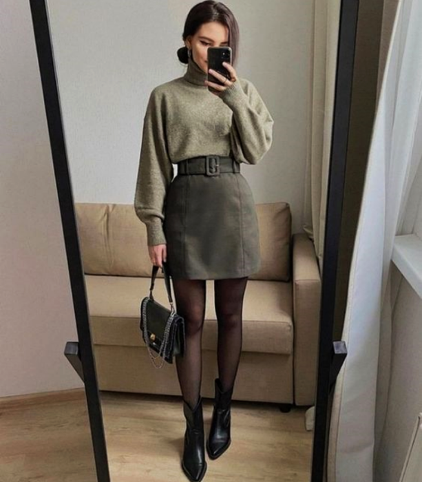 girl wearing a green sweatshirt, corduroy mini skirt, black tights and ankle boots