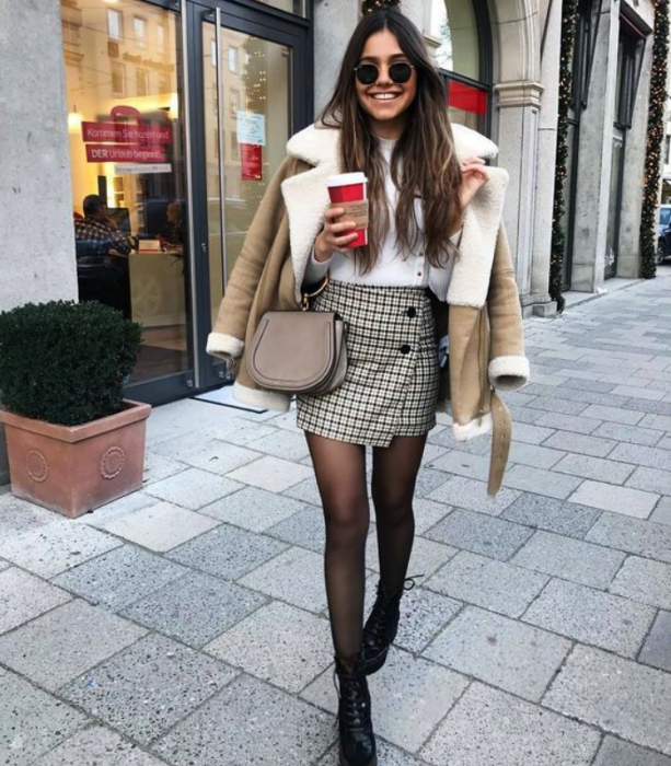 girl with long hair wearing sunglasses, white T-shirt, shearling jacket, dark stockings, white and black plaid skirt and ankle boots