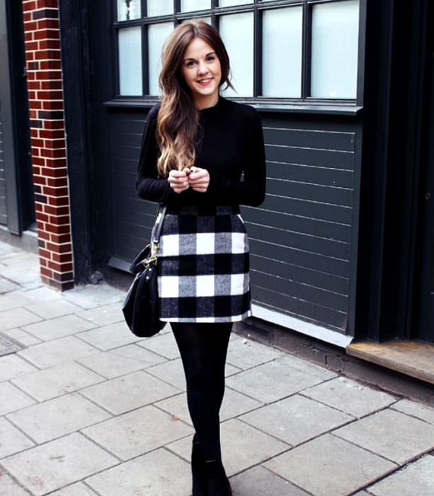 brown-haired girl wearing a long-sleeved t-shirt, black and white plaid miniskirt, black stockings and ankle boots