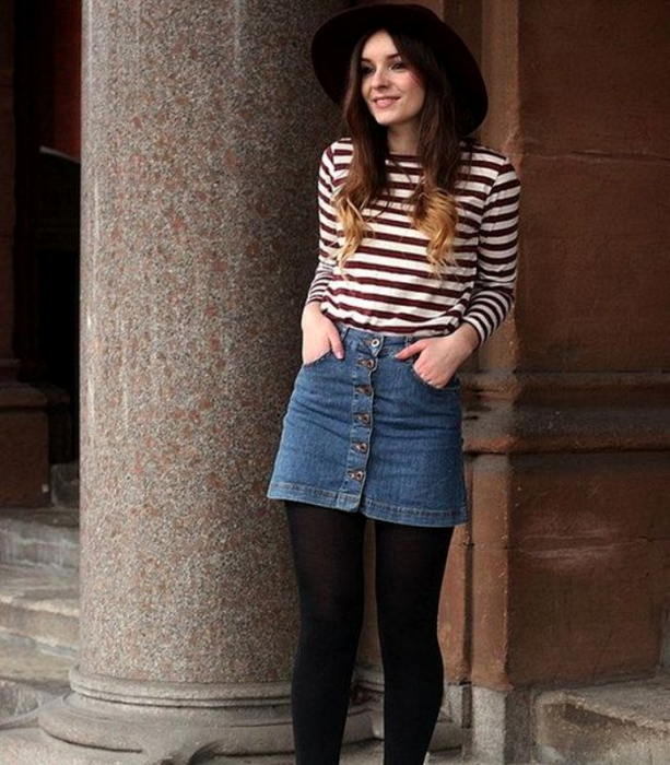 chica de cabello largo castaño usando un sombreo, camiseta de manga larga de rayas horizontales, minifalda de mezclilla, medias negras