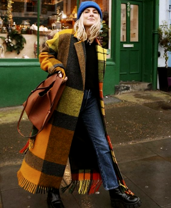 blonde girl wearing a blue beanie hat, yellow coat with black, brown and green plaid, black top, jeans, black thick-soled boots and brown tote bag