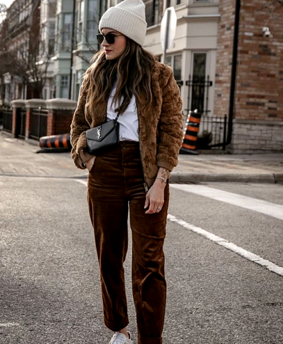 brown haired girl wearing sunglasses, light beige beanie hat, white top, brown teddy coat, brown corduroy pants, white tennis shoes and black mini bag