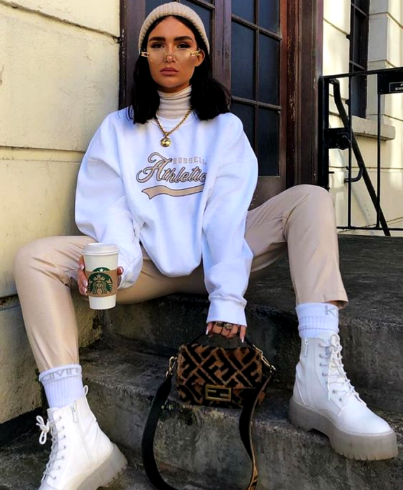 brown haired girl wearing glasses, beige beanie hat, white sweatshirt, beige pants, white transparent soled ankle boots and brown fenti bag