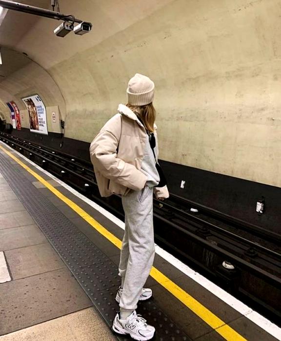 blonde girl wearing beige beanie, beige puffer jacket, gray sweatpants, gray sweatshirt, white chunky soled sneakers