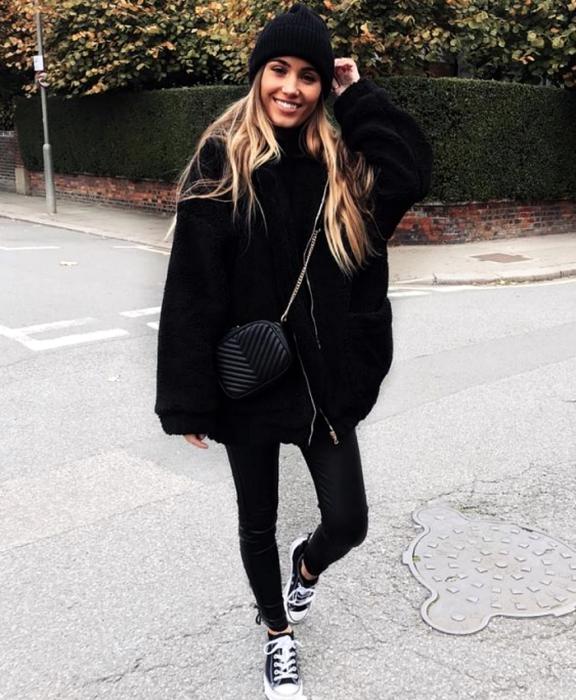 chica rubia usando un gorro beanie negro, abrigo oversized negro estilo teddy, leggings negros, tenis converse negros y bolso negro de piel