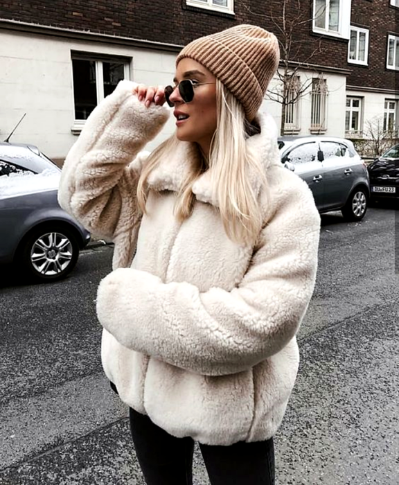 blonde girl wearing sunglasses, light brown beanie, white teddy jacket, black leggings