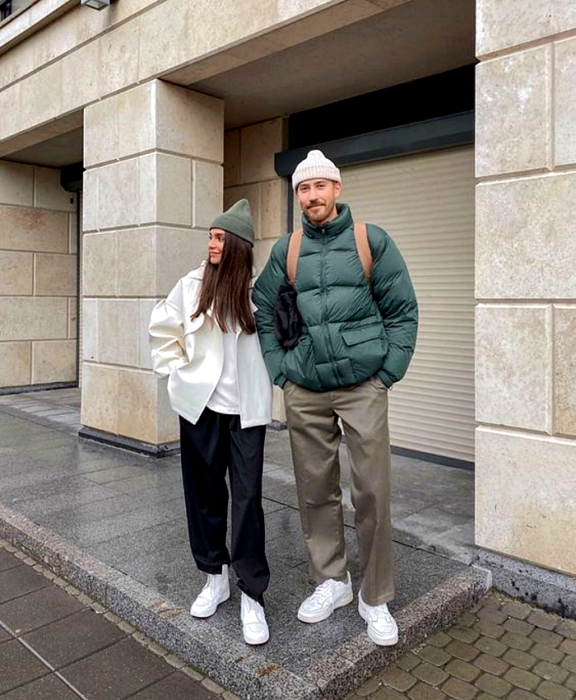 wedding couple, the girl with brown hair wearing a green beanie hat, white jacket, white top, navy blue pants, white tennis shoes and the boy wearing a white beanie hat, green puffer jacket, gray pants and white tennis shoes