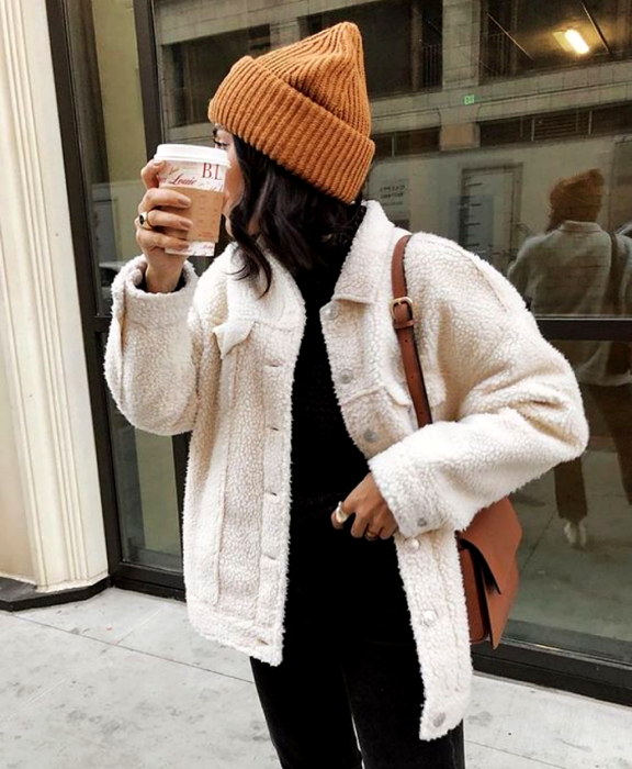 brown haired girl wearing brown beanie hat, white teddy coat, black turtleneck top and black jeans, brown bag
