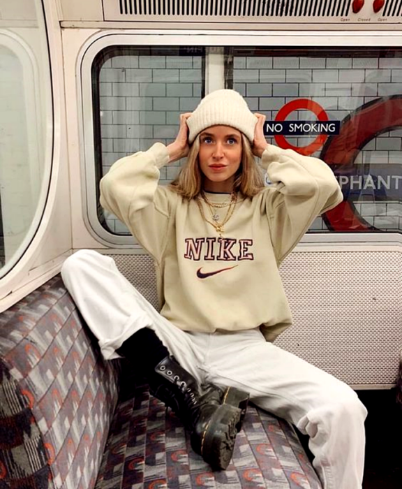 blonde girl wearing beanie white hat, beige nike sweatshirt, white pants, black leather boots with thick sole