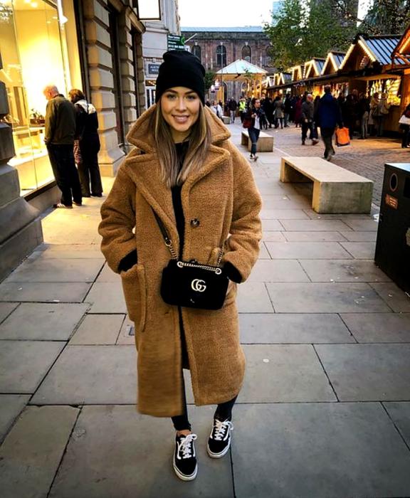 blonde girl wearing beanie black hat, brown teddy coat, black handbag, black skinny jeans, black converse sneakers
