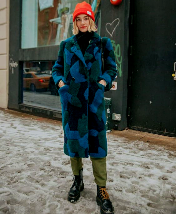 blonde girl wearing orange beanie hat, blue with green and black teddy coat, black pants, black thick soled leather boots