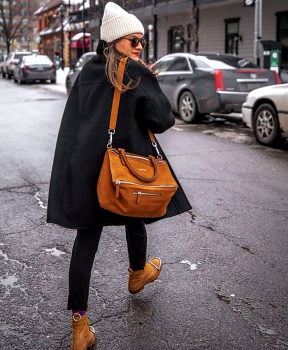 light haired girl wearing beanie white hat, black coat, large brown bag, black skinny jeans and brown ankle boots