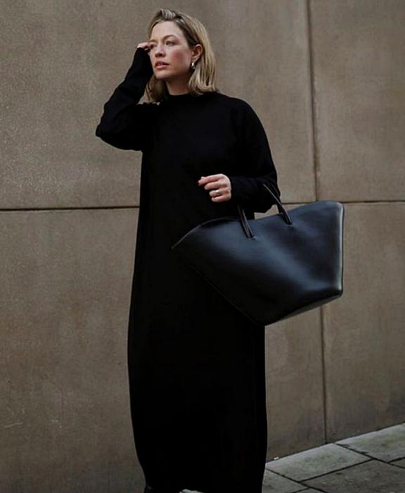 blonde girl wearing long-sleeved black knit dress, big black handbag