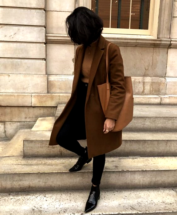 brown haired girl wearing beige top, long brown coat, brown leather bag, black skinny jeans and black pointed ankle boots