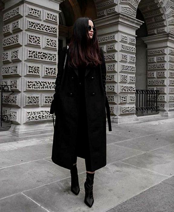 brown haired girl wearing sunglasses, black top, black coat, black skinny jeans, black high heel ankle boots and black handbag