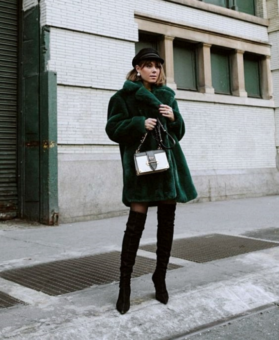 brown-haired girl wearing a black beret, long green furry coat, long black high-heeled boots, black stockings and white handbag with black